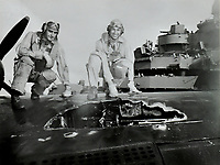 ARM Albert N. Barre and Pilot Lt. Commander Arthur L. Maltby, Jr. show the wing damage on their SB2C #70 after an attack over Maizura Harbor, Honshu, Japan.  -  July 30, 1945
