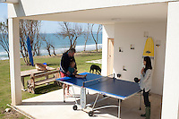 A sheltered porch below a roof terrace provides an outdoor room for table tennis and games when the weather is bad