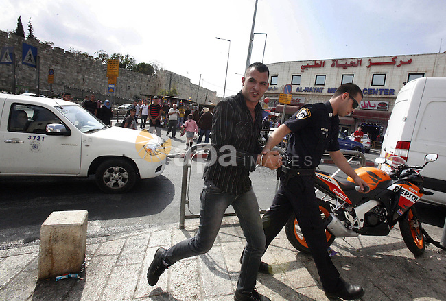 An Israeli police officer detains a Palestinian man at the main market of Jerusalem's old city ahead of Muslim festival of Eid al-Adha on October 22, 2012. Photo by Mahfouz Abu Turk