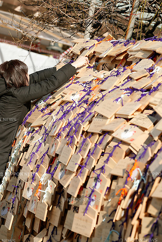 A woman ties a wooden votive plaque at Yushima Tenjin Shrine on January 12, 2017, Tokyo, Japan. Nestle's Kit Kat product is popular with students because its pronunciation in Japanese sounds like ''Kitto Katsu'' which means ''surely win''. Every year Japanese students tie hand-written wishes and messages at the shrine, wishing for luck in passing entrance exams to high school and colleges. The Yushima Tenjin Shrine is dedicated to the god of learning. (Photo by Rodrigo Reyes Marin/AFLO)