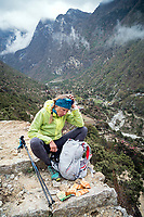 Kim Strom, exhausted, sits resting near Thamo before finishing up the last kilometers of running the 3 Passes Tour, Nepal.