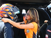 Aug. 1, 2014; Kent, WA, USA; Crew member Jianna Salinas helps father NHRA top fuel dragster driver Mike Salinas get dressed in his safety gear during qualifying for the Northwest Nationals at Pacific Raceways. Mandatory Credit: Mark J. Rebilas-
