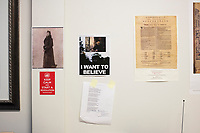 "A poster and a poem hang on a wall in the office of Anthony Amore, the Directory of Security and Chief Investigator at the Isabella Stewart Gardner Museum in Boston, Mass., USA, seen here on Tues., Dec. 5, 2017. The poster on top, reminiscent of Fox Mulder's ""I Want to Believe"" poster in the X-Files, features a reproduction of Manet's ""Chez Tortoni"" in place of the UFO. The poem is a piece written by John Updike about the Gardner Museum theft.  Part of Amore's ongoing work is the investigation into the 1990 theft of 13 pieces from the museum: 10 paintings, 2 objects, and 1 etching. Among the paintings stolen were works by Rembrandt, Vermeer, Degas, and Manet. ""Chez Tortoni"" is one of the paintings that was stolen in the heist. At left, is a portrait of Isabella Stewart Gardner."