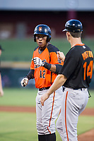 AZL Giants first baseman Beicker Mendoza (12) fist bumps first base coach Bill Horton (14) after a single against the AZL Cubs on July 17, 2017 at Sloan Park in Mesa, Arizona. AZL Giants defeated the AZL Cubs 12-7. (Zachary Lucy/Four Seam Images)