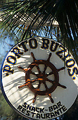 Buzios, Brazil. Sign for Porto Buzios snack bar and restaurant with palm leaves. Rio de Janeiro State.