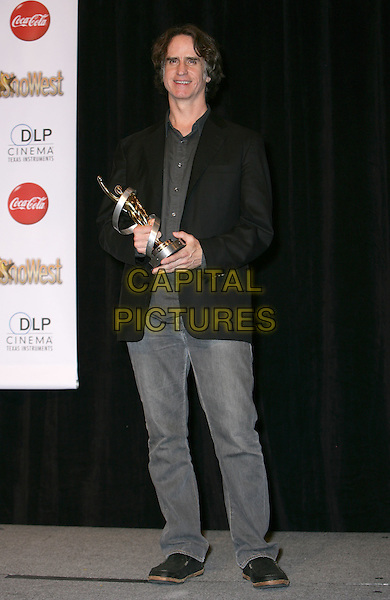 JAY ROACH .SHOWEST Final Night Talent Awards at the Paris Resort Hotel and Casino,  Las Vegas, Nevada , USA,.18th March 2010..full length black jacket blazer grey gray denim jeans shirt award winner trophy .CAP/ADM/MJT.© MJT/AdMedia/Capital Pictures.