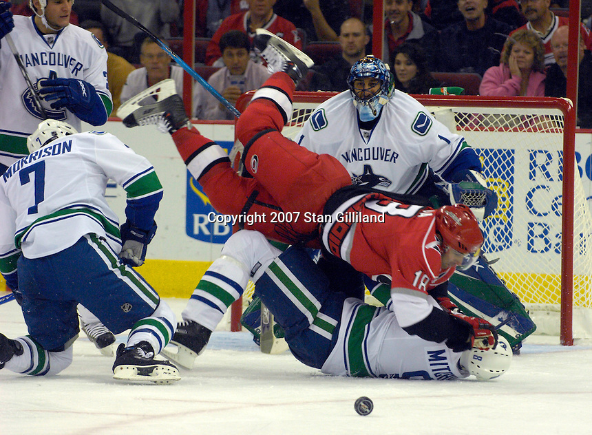 Carolina Hurricanes Ryan Bayda (18) jumps over the Vancouver Canucks' Brendan Morrison (7) and Willie Mitchell, below, as goaltender Roberto Luongo watches during their game Monday, Oct. 22, 2007 in Raleigh, NC. The Hurricanes won 3-1.