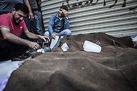 Syrian civilians bawl bereaved as they cry out woeful in front of the dead bodies of their relatives loaned on the street, who were killed during an aircraft shelling carried out by Assad's air force.