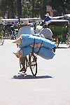A man carries baskets on his bike and rides through the streets in Marrakesh, Morocco.