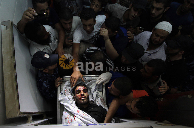 People mourn around the body of a Palestinian militant at a hospital morgue in Deir al-Balah in the central Gaza Strip July 6, 2014. Tensions were high along the Gaza border where Israel killed two Palestinian militants and wounded a third in one of about a dozen air strikes in response to rocket fire at southern Israeli towns. Hospital officials confirmed the fatalities, and the Israeli military confirmed it had bombed central Gaza. Photo by Ashraf Amra