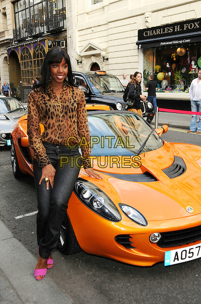 "KELLY ROWLAND .At the Lotus ""Project Eagle"" celebrity unveiling at London Transport Museum at the Covent Garden Piazza, London, England, UK, .July 16th 2008. .full length yellow orange fringe sitting on car leopard print top jeans pink shoes shirt .CAP/CAS.©Bob Cass/Capital Pictures."