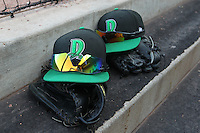 Dayton Dragons hats and gloves sit in the dugout during a game against the Lake County Captains at Fifth Third Field on June 25, 2012 in Dayton, Ohio. Lake County defeated Dayton 8-3. (Brace Hemmelgarn/Four Seam Images)