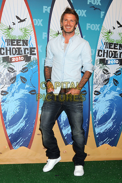 DAVID BECKHAM.Teen Choice Awards 2010 - Press Room held at Universal Studios Gibson Amphitheatre, Universal City, California, USA, 8th  August 2010..full length blue denim jeans trainers hands in pockets tattoos facial hair beard stubble grey gray white shirt smiling .CAP/ADM/BP.©Byron Purvis/AdMedia/Capital Pictures.