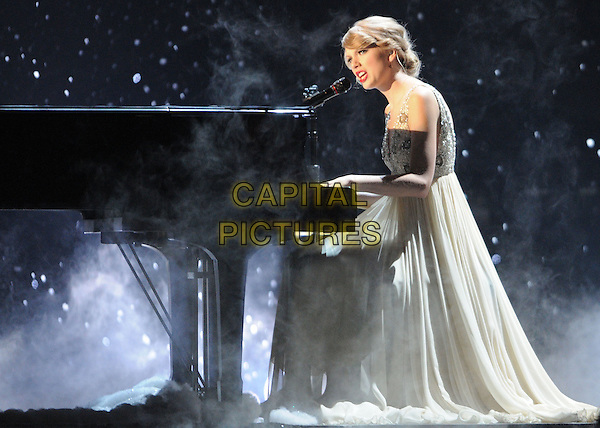 TAYLOR SWIFT.44th Annual CMA Awards, Country Music's Biggest Night, held at Bridgestone Arena, Nashville, Tennessee, USA.  .November 10th, 2010.stage concert live gig performance music full length dress singing grey gray silver sitting piano side profile .CAP/ADM/LF.©Laura Farr/AdMedia/Capital Pictures.