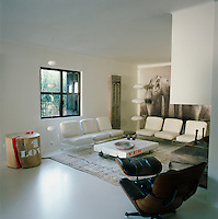White chairs and a black Eames lounge chair and ottoman are arranged around a low coffee table in a contemporary living room. A chunky piece of tree trunk acts as side table.
