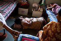 (L-R) Martha's daughter (9), Manjula Vinod Zala (27), Martha Sanjay Chauhan (purple) (35), and Haital Jagdishbhai Solanki, 24, (sister of Manjula Vinod Zala)...Women tell jokes and lounge around the surrogate house for their entire term of pregnancy while posters of babies and religious symbols adorn the walls together with calendars that they often use to count their days to the end of their terms. The women come to the house with just a small bag of clothes as everything else is provided for in the house...The Akanksha Infertility Clinic in Anand, Gujarat, India, is known internationally for its surrogacy program and currently has over a hundred surrogate mothers pregnant in their environmentally controlled surrogate houses.