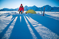 A woman stands next to her tent using a camp stove in the Jungfrau Region of Switzerland.