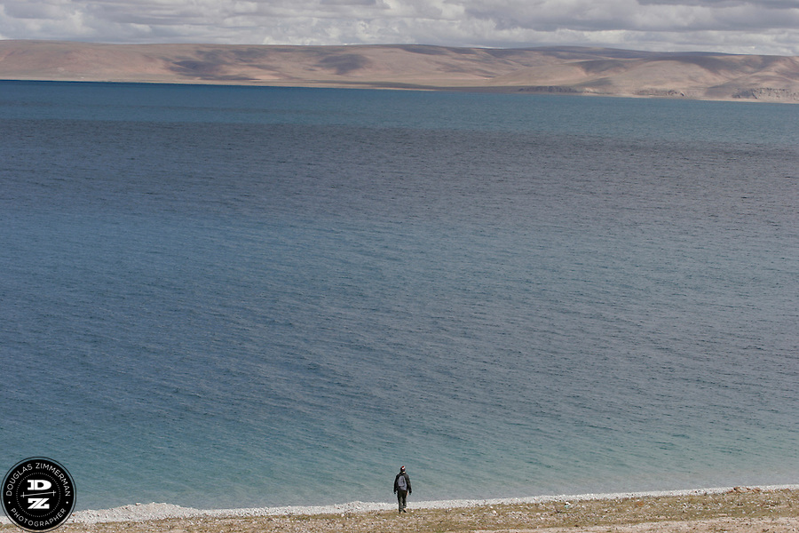 A hiker walks to the edge of Nam-tso, a lake that sometimes has water the shade of turquoise.  Nam-tso Lake is the second-largest saltwater lake in China, at over 70 kilometers in length and is located on the Tibetan plateau at an elevation of 4718 meters above sea level.  Photograph by Douglas ZImmerman