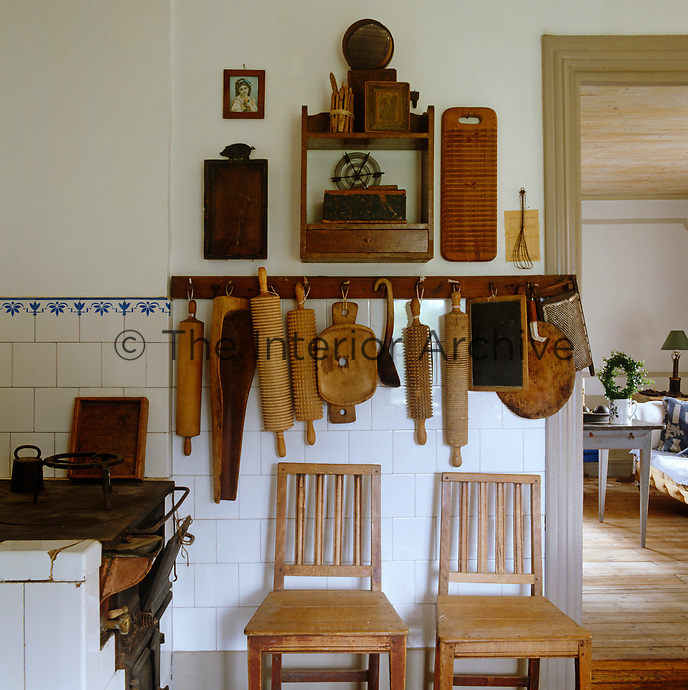 Detail of a wall in a rustic kitchen with a variety of rolling pins and other wooden utensils hanging from hooks
