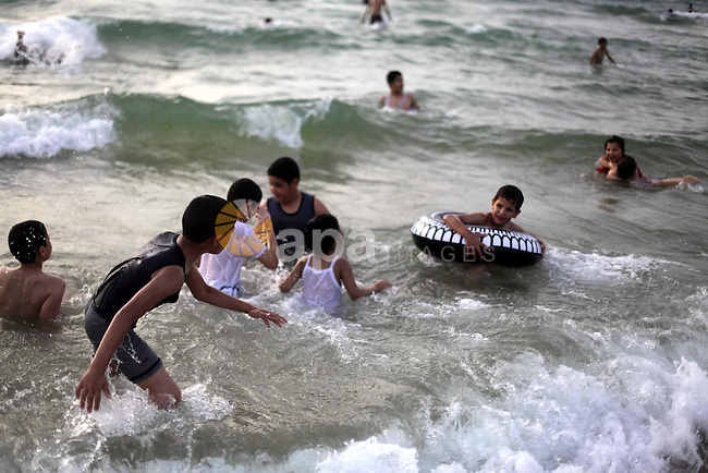 Palestinians enjoy swimming in the sea at Gaza beach during Friday holiday in Gaza city, May 24, 2013. Gazans escape to the beach and out from their homes during heat wave and power outages. Photo by Ashraf Amra