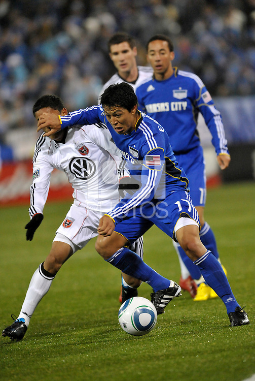 Roger Espinoza (17) holds off the challenge of Andy Najar...Kansas City Wizards defeated DC United 4-0 in their season opener, at Community America Ballpark in Kansas City, Kansas.