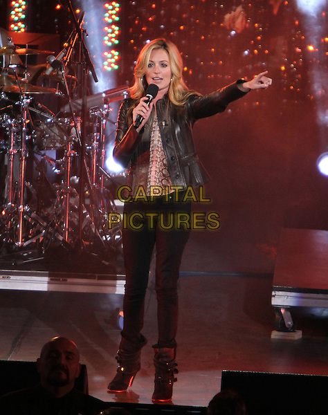 """Cat Deeley.Caesars Entertainment Kick-Off Of """"Escape To Total Rewards"""" , Los Angeles Show Held At Hollywood & Highland Center, Hollywood, California, USA, 1st March 2012..music concert gig live on stage  full length leather jacket jeans hand microphone boots .CAP/ADM/KB.©Kevan Brooks/AdMedia/Capital Pictures."""
