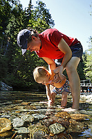 Mother holding daughter over Ohanapecosh River, Grove of the Patriarchs Trail, Mount Rainier National Park, Washington, USA<br />