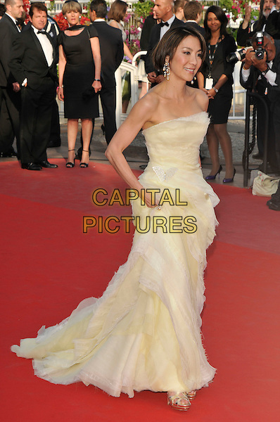 MICHELLE YEOH.Attending the 'Wall Street: Money Never Sleeps' film premiere held at the Palais des Festivals during the 63rd International Cannes Film Festival, Cannes, France.14th May 2010..full length strapless cream pale yellow tulle long maxi dress gown tiered layered layers walking .CAP/PL.©Phil Loftus/Capital Pictures.