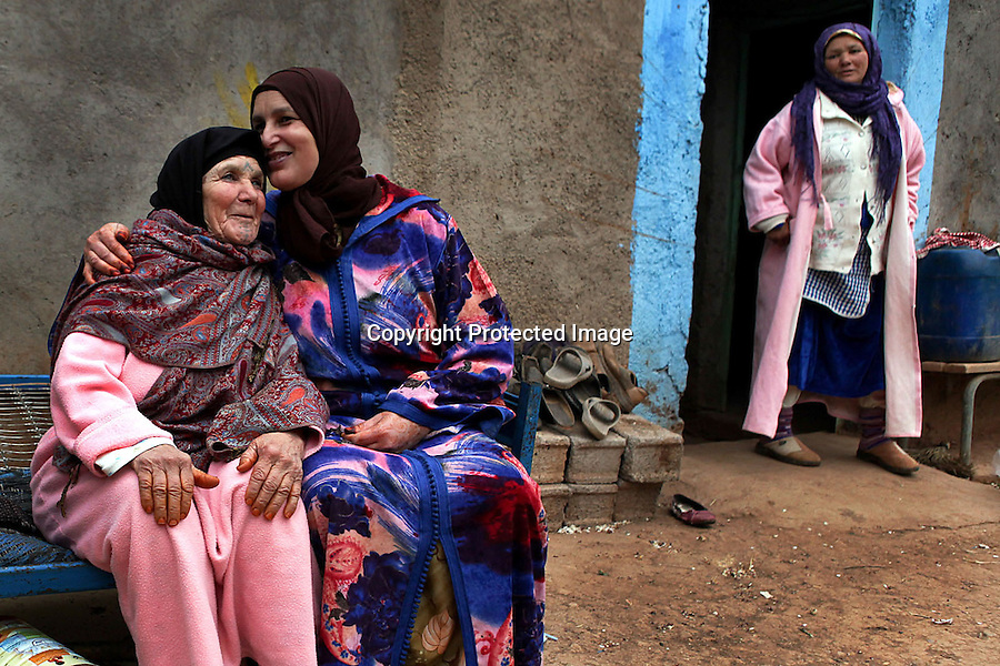 Khina Boujnoui and her daughter, Fatima, share a moment of affection outside the family's home in Tamda, Morocco. The women are part of a traditional Berber family that has been weaving for generations.