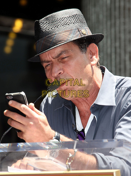 Charlie Sheen  .Slash Honored with Star on the Hollywood Walk of Fame, Hollywood, California, USA..July 10th, 2012.half length blue grey gray shirt hat podium speech mobile phone iphone .CAP/ADM/RE.©Russ Elliot/AdMedia/Capital Pictures.