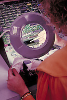 Electronics technician using magnifying lens for computer drive testing. Computers. Technology. Career. Occupation. California.