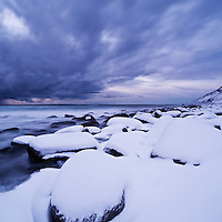 Snow covered rocks at Unstad beach, Vestvågøy, Lofoten islands, Norway