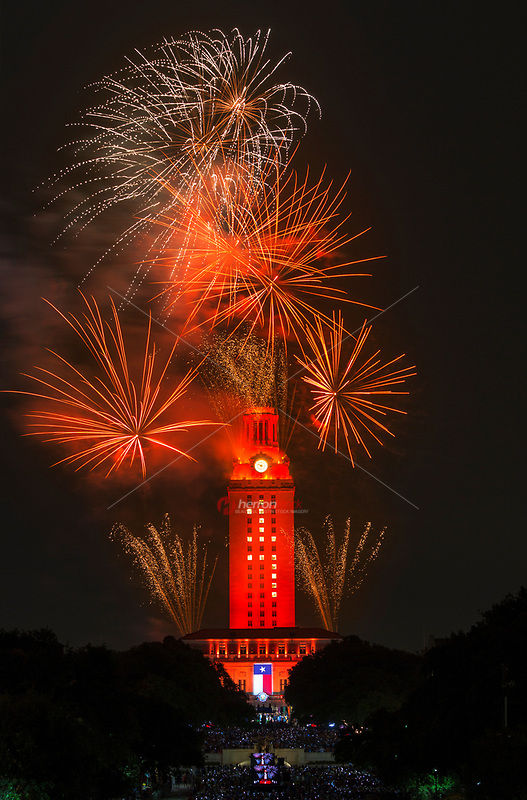 The University of Texas celebrates graduation at the 2017 spring commencement ceremonies with a stunning fireworks display of stunning vibrant exploding colors over the UT Tower lit in burnt orange.