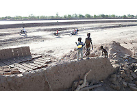 KOLONGO, MALI - FEBRUARY 24: Children play at some ruins where houses were destroyed to make way for a dam for a channel was built by Chinese for Libyan company that leases land from the Mali government on February 24 2011, outside Kolongo, Mali. (Photo by Per-Anders Pettersson