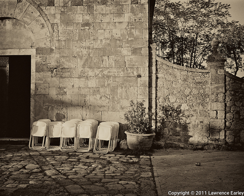 Plastic Chairs are gathered together after an afternoon fiesta.  The charming walled  town itself was built during the Middle Ages.