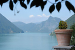 A view of Lake Lugano with a small fower pot in the foreground. View of Lake Lugano from Oria, a town in the mountains on Lake Lugano, Italy.