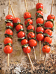 Five skewers of grilled cherry tomatoes and basil leaves, sprinkled with kosher salt.