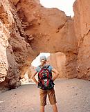 USA, California, young woman on Natural Bridge Canyon hike, Death Valley National Park