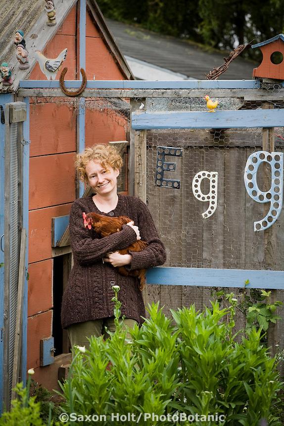 Author, Amy Stewart holding pet chicken in her whimsical backyard garden