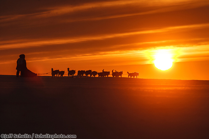 Karen Ramstead and her Siberian husky team mushes down the trail as the sun sets over the Bering Sea just a few miles from the finish line in Nome.