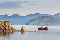 Fishing boat cruises the waters near the Kodiak harbor on the island of Kodiak, Alaska.
