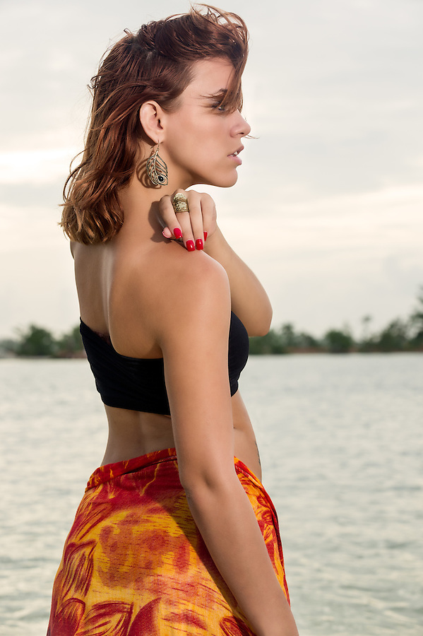 Young beautiful woman profile looking away in a tropical beach