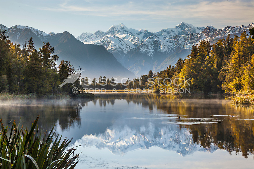 Misty morning and perfect reflections of Mt Cook, Mt Tasman & Southern Alps at Lake Matheson, Westland Tai Poutini National Park NZ.