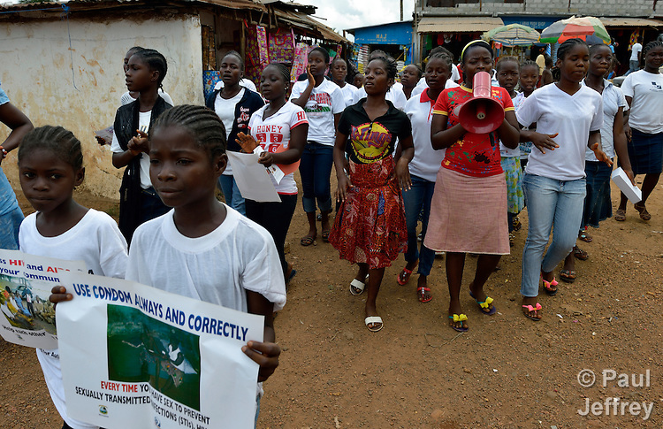 """Members of """"Daughters of the King,"""" a girls' organization that carries out public education about HIV and AIDS, marches through the market in Kakata, Liberia, singing and chanting about the disease and how to prevent it. The group  is sponsored by the HIV/AIDS Program of the Lutheran Church in Liberia."""