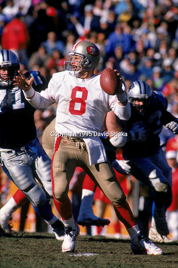 San Francisco 49ers quarterback Steve Young looks for a receiver during an NFL football game against the Carolina Panthers at Memorial Stadium on December 10, 1995 in Clemson, South Carolina. The 49ers won 31-10. (Photo by David Stluka)