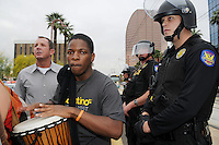 Phoenix, Arizona. April 25, 2012 - Jarvis Johnson plays a drum in the middle of northbound Central Avenue in Phoenix moments after a group of anti-SB 1070 protesters blocked the street in protests against ICE's policies. . About 500 people protested the controversial law on the same day U.S. Supreme Court justices heard legal arguments on the Arizona vs. United States case. At the end of the march, six activists blocked Central Avenue by sitting in the middle of the street. They all were arrested by the Phoenix Police Department and taken to the Fourth Avenue County Jail. Photo by Eduardo Barraza © 2012
