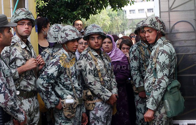 Egyptian soldiers stand guard as voters queue outside a school turned polling station in Cairo on November 28, 2011. Egyptians began voting in the first elections since the fall of autocrat Hosni Mubarak who was ousted in February in one of the most important moments of the Arab Spring..Photo by Ashraf Amra