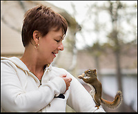 "BNPS.co.uk (01202 558833).Pic: NancyRose/BNPS..***Please Use full byline***..Nancy with one of her 'actors' in the back garden of her home...Ready for my close-Nut!..A group of wild squirrels have been snapped posing with human objects for a hilarious set of adorable photographs...Nancy Rose, 58, was inspired to take the quirky images when she spotted a squirrel sitting on top of a pumpkin she had left in her garden...She began building her own 'props' for the creatures to interact with, and left miniature items outside surrounded by nuts on her garden decking to entice them closer...She created a tiny washing machine, tumble dryer, hats, coats, musical instruments, easel and paint pallette, a boat and a fire place and waited for the animals to visit...The inquisitive squirrels have gradually learnt that they find nuts if they pick up or look inside the items, and have started frequenting the garden more often...Nancy patiently waits with her camera and takes more than 100 frames of each squirrel as they move incredibly fast...Nancy, a school counsellor from Nova Scotia in Canada said: ""My squirrel pictures started almost by accident."