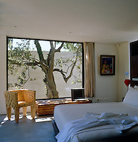 A picture window in the bedroom frames an old tree in the garden and the curtains are of weighted parachute silk and run on wire cables