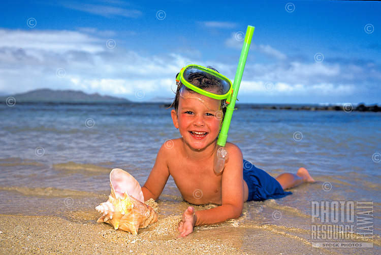 A young boy ( age 7 )  enjoys playing with a conch shell and snorkeling in Hawaii's warm blue waters.
